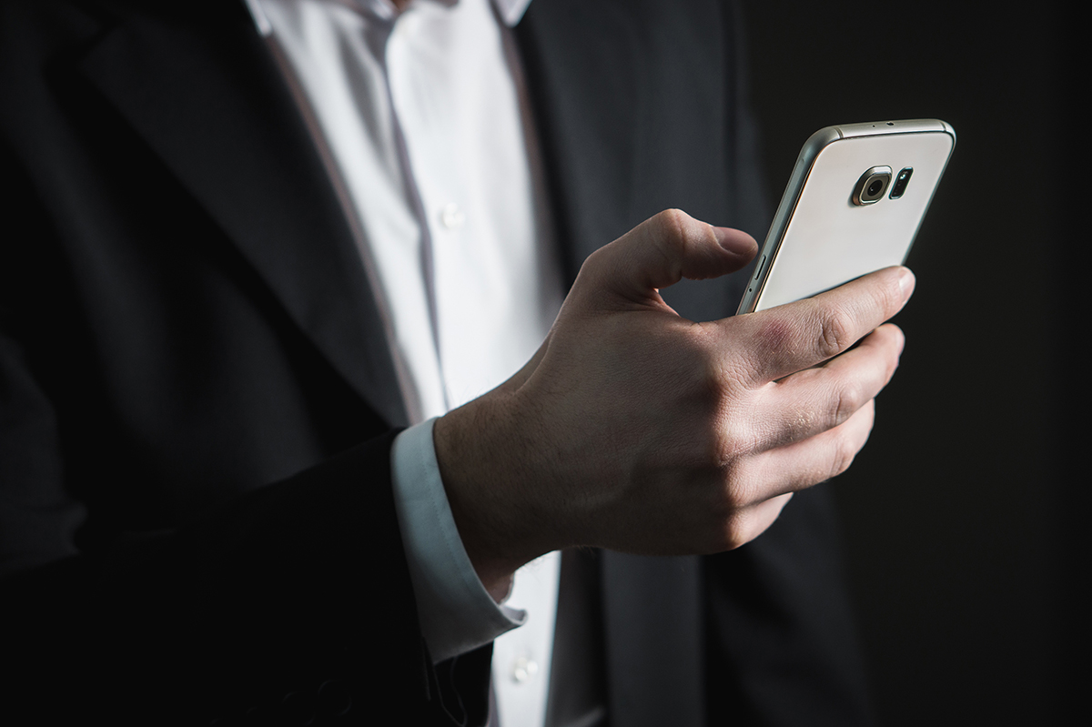 The picture shows a businessman with his smartphone in his hand regarding costs and benefits of Cyber Security.